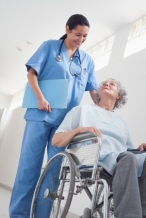 Elderly patient in a wheelchair next to a nurse in hospital ward