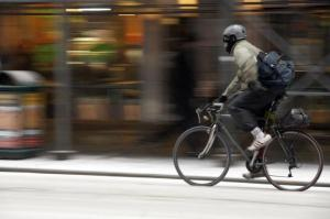 A bicyclist rides through a snowy street during the morning rush hour in New York